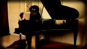 Franzi an einem Piano, neben ihr steht ein Affe